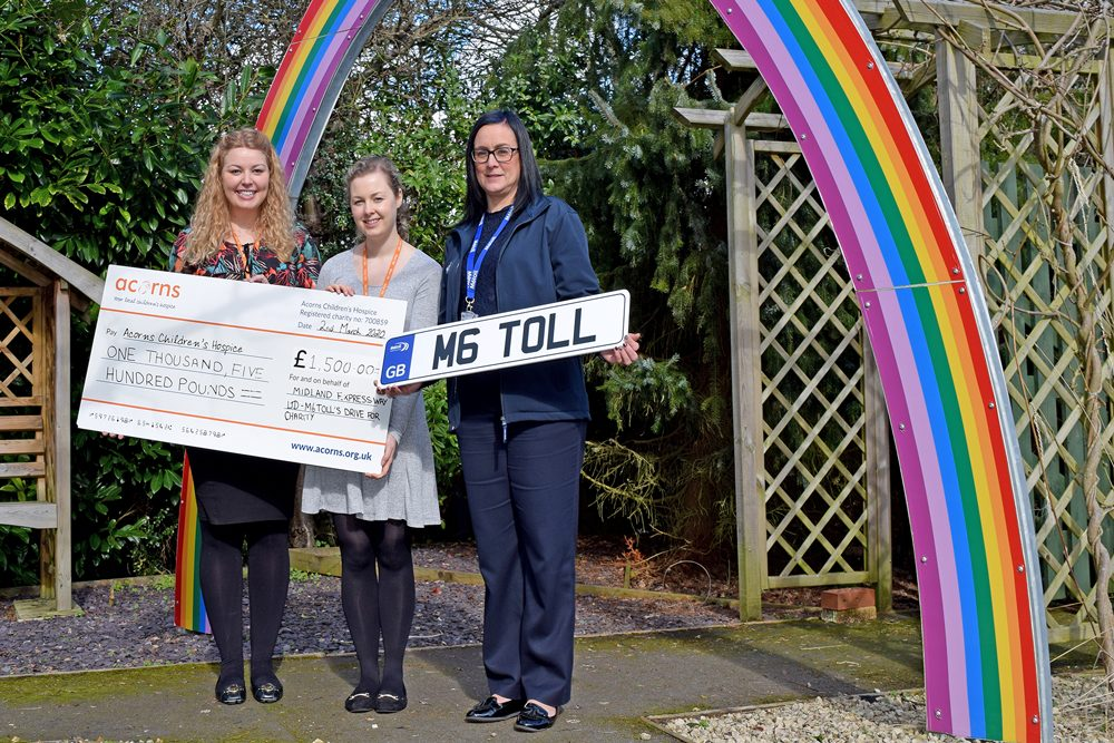 M6toll employee holding M6toll sign poses next to two ladies from Acorns Hospice with giant cheque